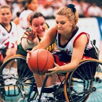 Australian women's wheelchair basketballer Amanda Carter challenges for the ball in a game against the USA at the 1996 Atlanta Paralympic Games